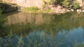 Lago nella cava di pietra con le rive rocciose vento molle che si muove attraverso i giovani alberi sottili stock footage