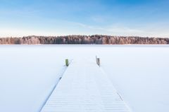 Lago nevado congelado e um cais fotografia de stock