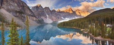 Lago no nascer do sol, parque nacional moraine de Banff, Canadá