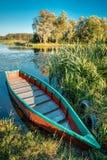 Lago o río y barco de pesca azul de madera viejo del rowing en hermoso Fotografía de archivo