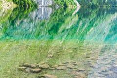 Lago Obersee con chiara acqua verde e la riflessione, parco nazionale di Berchtesgaden Immagini Stock