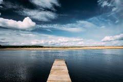 Lago ou rio velho pier On Calm Water Of das placas de madeira na noite Fotos de Stock
