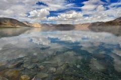 Lago Pangong delle alte montagne: il lago è chiara e superficie blu, calma come specchio e riflette le molti nuvole e cielo blu i Fotografie Stock