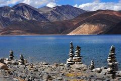 Lago Pangong high mountain: nella priorità alta sulla riva è lo stupa buddista di pietra, lago dell'acqua blu con la riflessione  Fotografie Stock Libere da Diritti