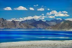 Lago Pangong in un giorno soleggiato luminoso: acqua blu con le bande più scure, montagne, nuvole bianche del cielo blu, nella sa Fotografie Stock