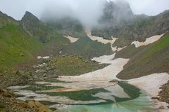 Lago parcialmente congelado Didighali com uma passagem de montanha no fundo em uma fuga de caminhada nas montanhas de Cáucaso que fotografia de stock