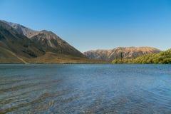 Lago Pearson e montagna con la chiara terra del nero del cielo blu, Nuova Zelanda immagini stock libere da diritti