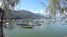 Lago Pheva de los barcos turísticos de Multicolore, montaña y árboles almacen de video