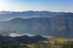 Lago Phewa y ciudad de Pokhara en un valle verde de la montaña con niebla Silueta del hombre de negocios Cowering imagen de archivo libre de regalías