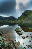 Lago prístino del glaciar en las montañas y las nubes de tormenta Fotos de archivo libres de regalías