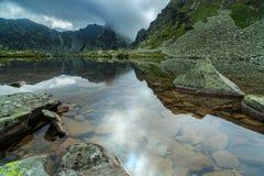 Lago prístino del glaciar en las montañas y las nubes de tormenta Fotografía de archivo
