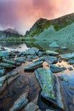 Lago prístino del glaciar en las montañas y las nubes de tormenta en la puesta del sol Imagen de archivo