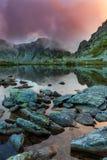 Lago prístino del glaciar en las montañas y las nubes de tormenta en la puesta del sol Imagen de archivo libre de regalías