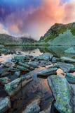 Lago prístino del glaciar en las montañas y las nubes de tormenta en la puesta del sol Fotos de archivo libres de regalías
