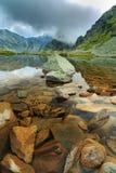 Lago prístino del glaciar en las montañas y las nubes de tormenta en la puesta del sol Imagenes de archivo
