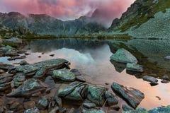 Lago prístino del glaciar en las montañas y las nubes de tormenta en la puesta del sol Foto de archivo