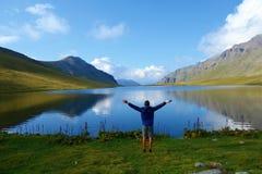 Lago preto rock com um homem novo e reflexões de montanhas circunvizinhas no parque nacional de Lagodekhi situado em montanhas de imagens de stock