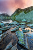 Lago Pristine da geleira nos cumes e nas nuvens de tempestade no por do sol Imagem de Stock