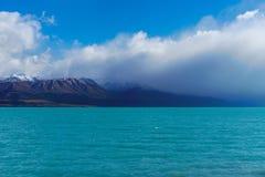 Lago Pukaki in Nuova Zelanda con il suo contesto della montagna Fotografia Stock