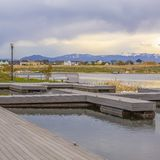 Lago quadrado frame com plataforma de madeira e bancos que negligenciam casas além da costa gramínea imagem de stock