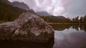 Lago que refleja la naturaleza en el medio de las montañas italianas almacen de video