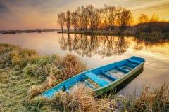 Lago, río y barco de pesca azul de madera viejo del rowing en la salida del sol hermosa Imagen de archivo