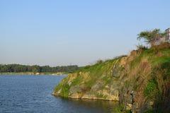 Lago rocoso con algunas piedras e hierba en el banco foto de archivo