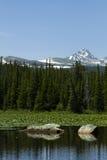 Lago rosso drammatico rock con le pietre, la foresta e le montagne enormi Immagine Stock Libera da Diritti