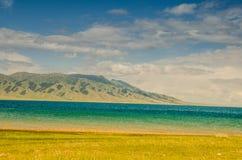 Lago Sayram pelo prado, no platô Imagem de Stock