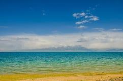 Lago Sayram pelo prado, no platô Foto de Stock Royalty Free
