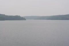Lago scuro nebbioso Immagini Stock