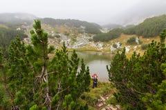 Lago seguente stante della montagna di viaggiatore con zaino e sacco a pelo della donna Fotografia Stock