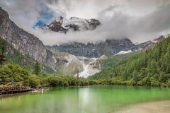 Lago sotto la montagna della neve nel Tibet Immagini Stock