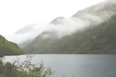 Lago sotto le montagne nebbiose Immagine Stock Libera da Diritti