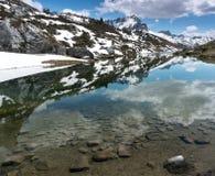 Lago splendido della montagna nelle alpi con le riflessioni ed i resti della neve Fotografie Stock Libere da Diritti