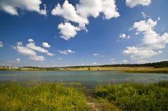 Lago summer vicino al villaggio del paese Immagine Stock