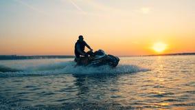 Lago sunset con un hombre que conduce a lo largo de él en su waterbike, esquí del jet almacen de metraje de vídeo