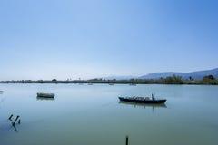 Lago tranquilo con dos barcos de pesca Laguna del agua dulce en Estany de Cullera Valencia, España Fotos de archivo