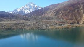 Lago tranquilo con la montaña enorme de la nieve Foto de archivo libre de regalías