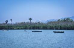Lago tranquilo con los barcos de pesca Laguna del agua dulce en Estany de Cullera Valencia, España Imagen de archivo libre de regalías