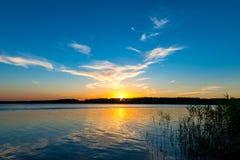 Lago tranquilo e o sol de ajuste Fotografia de Stock