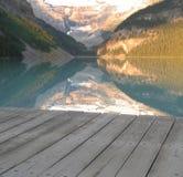 Lago tranquilo en la parte inferior de montañas con el muelle Fotografía de archivo libre de regalías