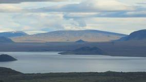 Lago tranquilo hermoso y montaña coronada de nieve enorme en horizonte, nubes pintorescas metrajes