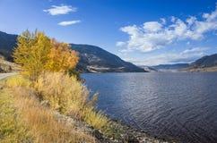 Lago tranquilo sob um céu azul ensolarado nebuloso Foto de Stock