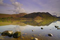 Lago Ullswater que enfrenta montanhas com céu nebuloso foto de stock royalty free
