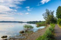 Lago varese con l'isolotto della Virginia e un allungamento della pista ciclabile pedonale intorno al lago, Biandronno, Italia Fotografia Stock