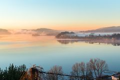 Lago Varese, Gavirate, provincia di Varese, Italia del nord Alba pittoresca con nebbia Immagini Stock