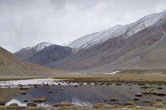 Lago vicino alle montagne ricoperte neve Fotografia Stock Libera da Diritti