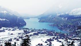 Lago y aldea alpestres en el invierno (Suiza) Imagenes de archivo