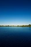 Lago y cielo azul Fotos de archivo